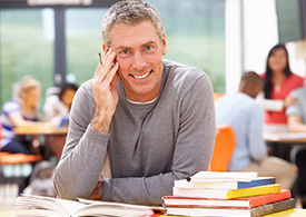 adult male smiling and studying in library