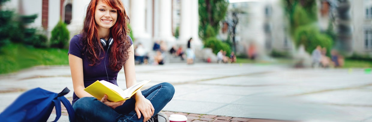 college woman with book sitting on sidewalk